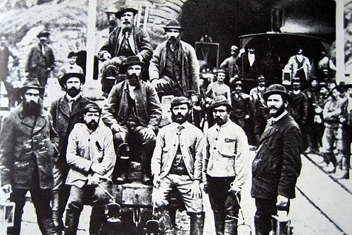 Bauarbeiter um 1880 vor dem Südportal des Gotthardtunnels in Airolo. Quelle: https://de.wikipedia.org/wiki/Gotthardtunnel